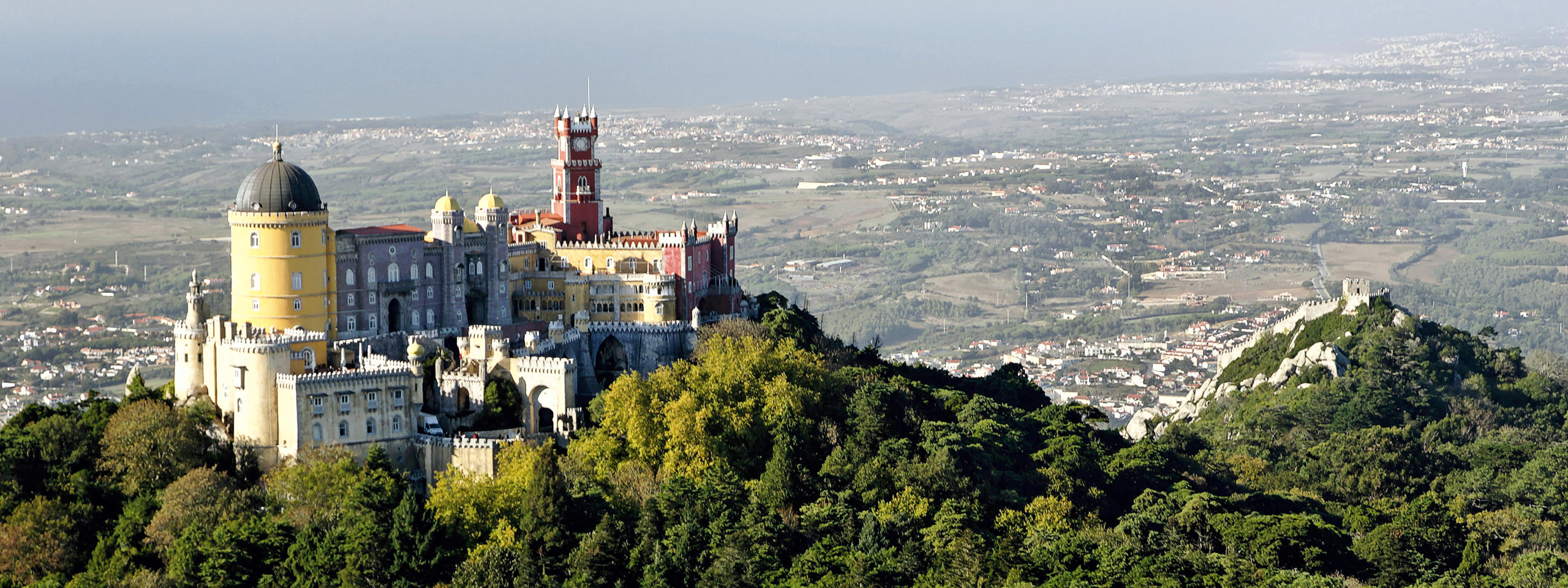 Birdview of Pena palace with the ocean in the background and the Moorish Castle on the right
